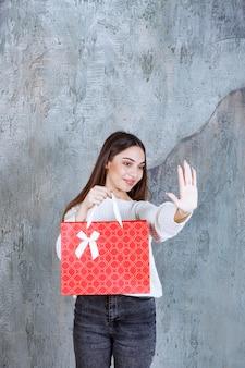 Menina de camisa branca segurando uma sacola de compras vermelha e parando outras pessoas.