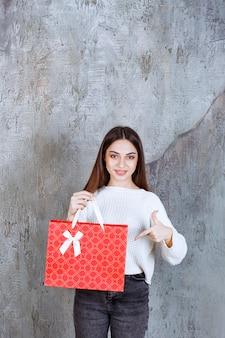 Menina de camisa branca segurando uma sacola de compras vermelha.
