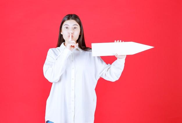 Menina de camisa branca segurando uma seta apontando para a direita e pedindo silêncio ou sussurrando