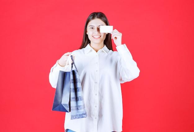 Menina de camisa branca segurando várias sacolas de compras e apresentando seu cartão de visita