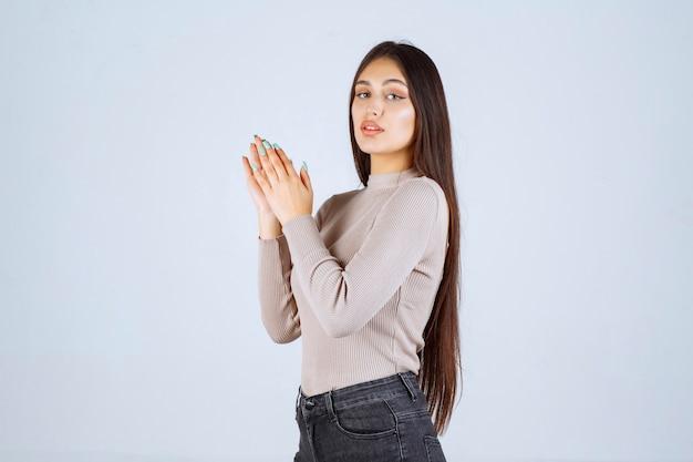 Menina de camisa cinza aplaudindo algo.