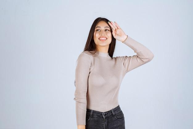 Menina de camisa cinza dando poses positivas e atraentes.