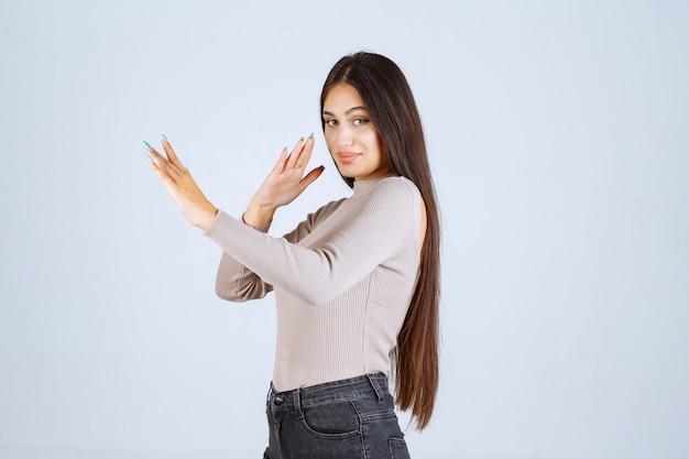 Menina de camisa cinza, impedindo algo.
