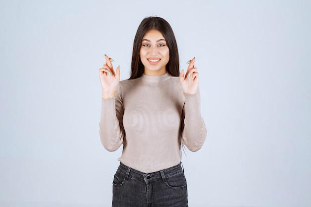Menina de camisa cinza, mostrando o dedo cruzado.