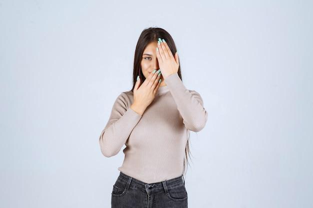 Menina de camisa cinza, olhando por entre os dedos.