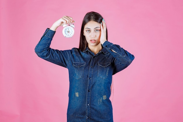 Menina de camisa jeans segurando o despertador e cobrindo a orelha por causa do anel