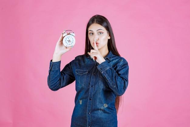 Menina de camisa jeans segurando o despertador e fazendo sinal de silêncio