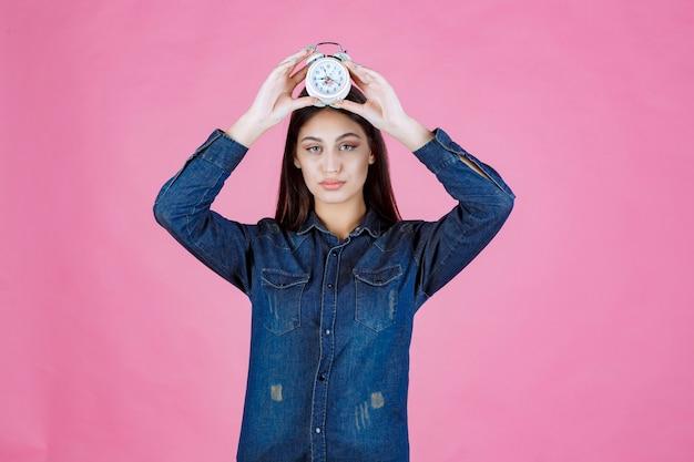 Menina de camisa jeans segurando o despertador na cabeça