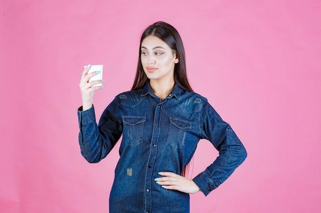 Menina de camisa jeans segurando uma xícara de café e se sentindo positiva