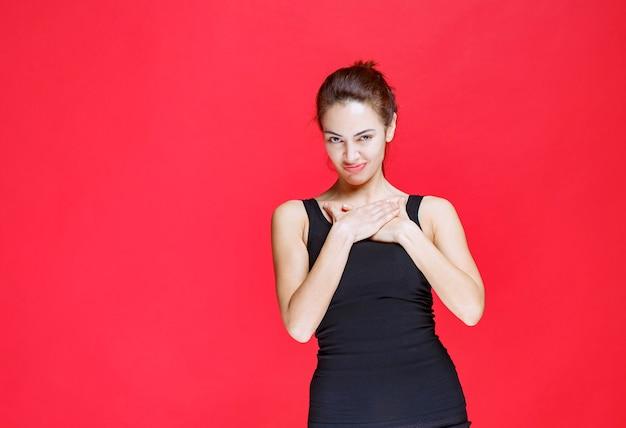 Menina de camisa preta, apontando para si mesma. foto de alta qualidade