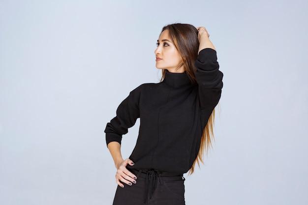 Menina de camisa preta dando poses de apelação para foto de capa de mídia social. foto de alta qualidade