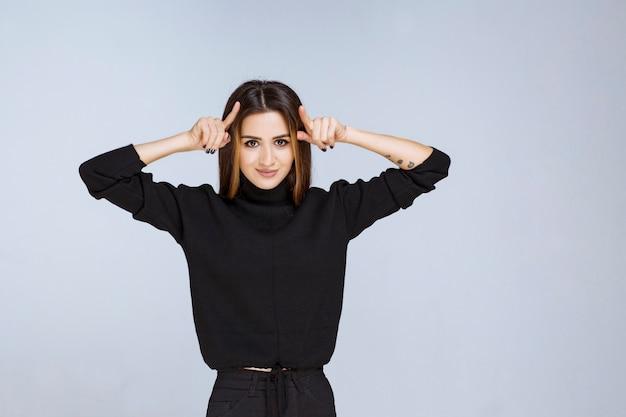 Menina de camisa preta, mostrando sinal de orelha de coelho. foto de alta qualidade