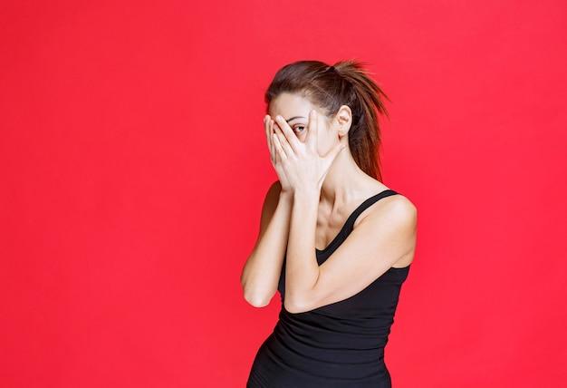 Menina de camisa preta olhando por entre os dedos. foto de alta qualidade