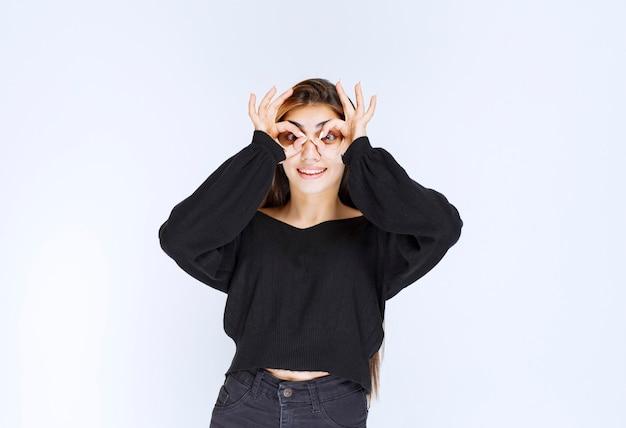 Menina de camisa preta olhando por entre os dedos.