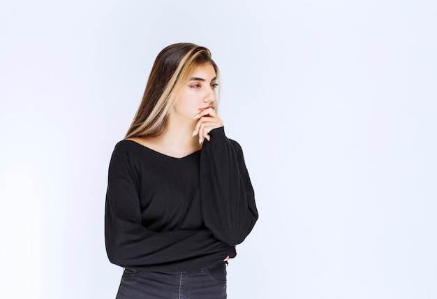 Menina de camisa preta parece pensativa.