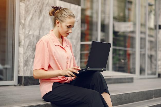 Menina de camisa rosa, sentado perto de casa e usar o laptop