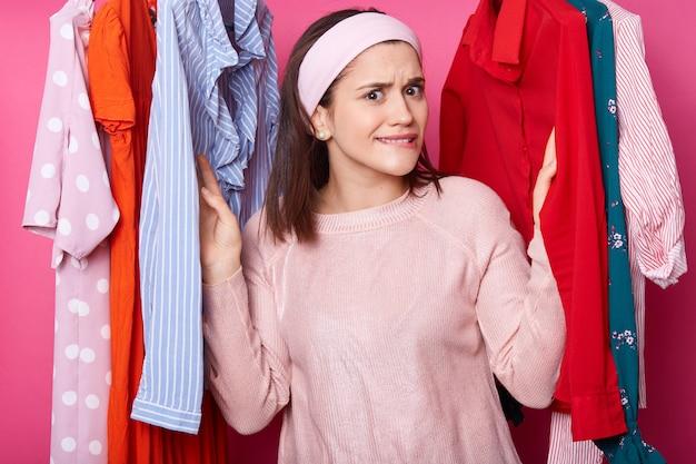 Menina de camisa rosa tem compras na boutique de moda. moça bonita escolhe o vestido na loja de roupas. mulher encontra vestido moderno enquanto curvando os lábios. chateado feminino não gosta de blusas.