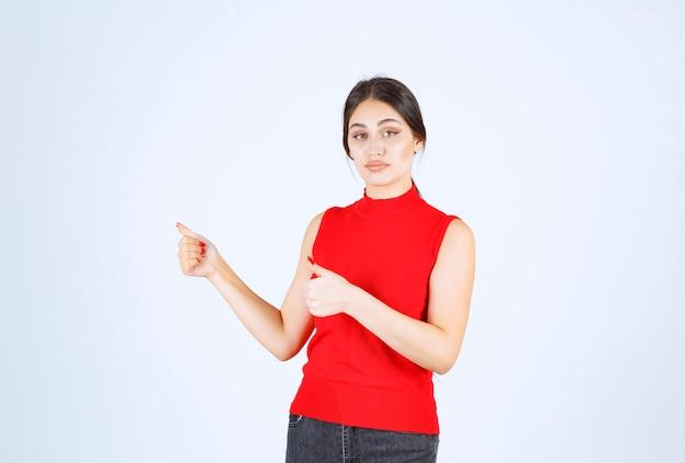 Menina de camisa vermelha aparecendo os polegares.