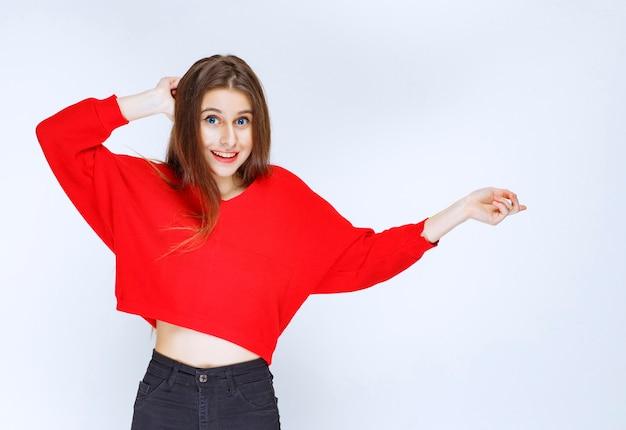 Menina de camisa vermelha, apontando para o lado direito.