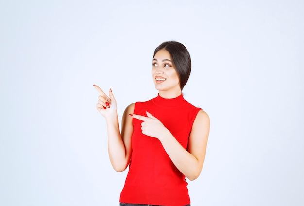 Menina de camisa vermelha, apontando para o lado esquerdo.