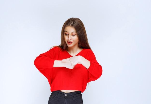 Menina de camisa vermelha, apontando para o relógio.