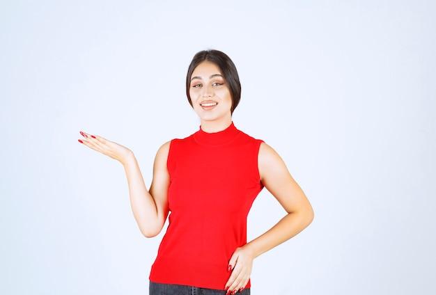 Menina de camisa vermelha, apresentando e mostrando algo na mão.