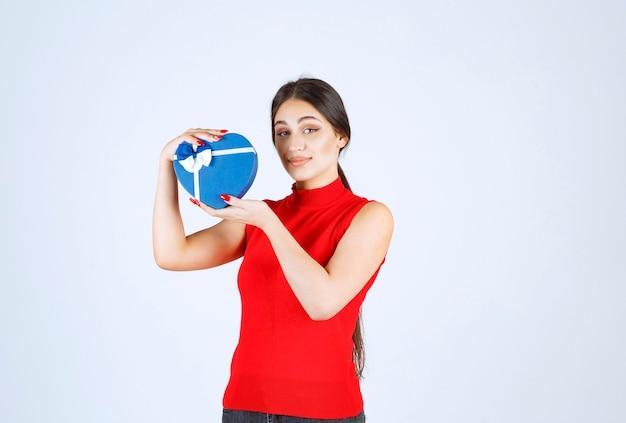 Menina de camisa vermelha, apresentando sua caixa de presente de forma de coração azul.