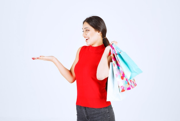 Menina de camisa vermelha carregando sacolas coloridas atrás do ombro.