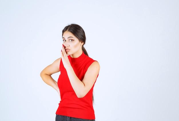 Menina de camisa vermelha, colocando a mão na boca e sussurrando.