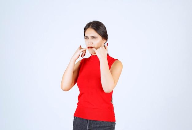 Menina de camisa vermelha colocando as mãos na boca e assobiando.