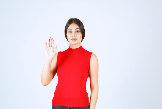Menina de camisa vermelha, cumprimentando ou convidando alguém.
