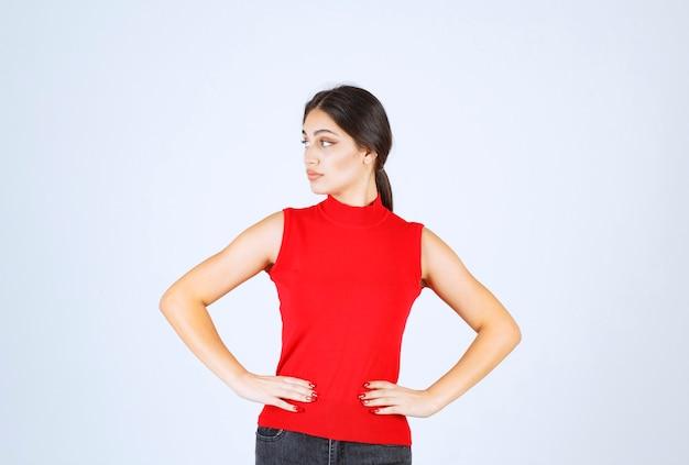 Menina de camisa vermelha dando poses positivas e sedutoras.