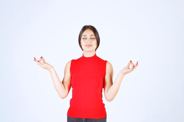 Menina de camisa vermelha fazendo meditação.
