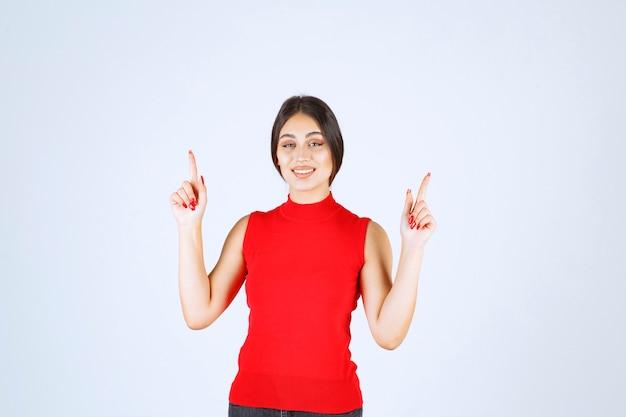 Menina de camisa vermelha, levantando a mão e apontando acima.