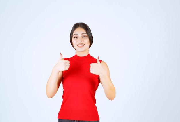Menina de camisa vermelha, mostrando sinal de mão de prazer.