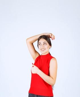 Menina de camisa vermelha, mostrando sinal positivo com a mão.