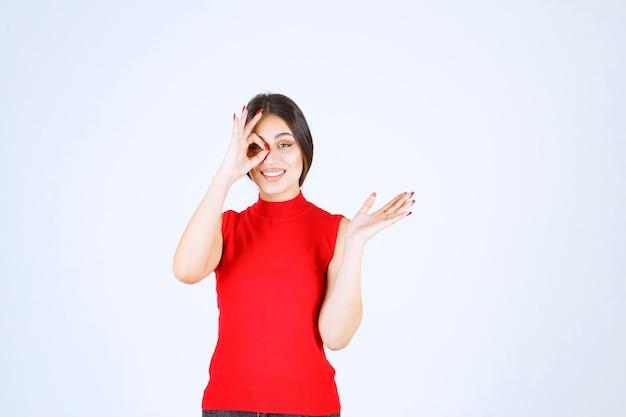 Menina de camisa vermelha, olhando por entre os dedos.