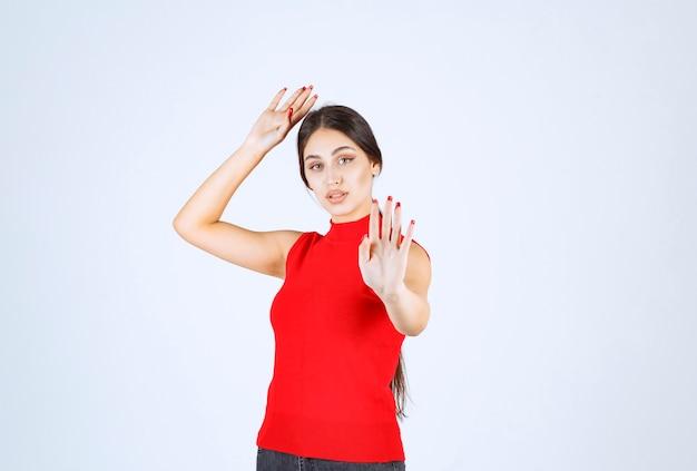 Menina de camisa vermelha parando alguém.