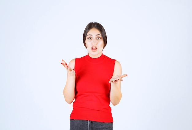 Menina de camisa vermelha parece estressada e nervosa.