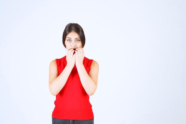 Menina de camisa vermelha parece triste e desapontada.