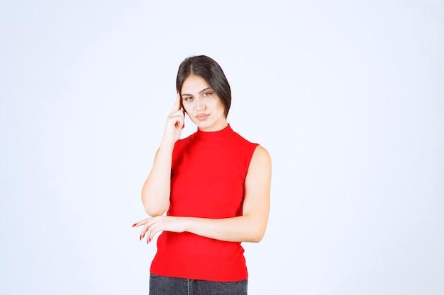 Menina de camisa vermelha, pensando e analisando.