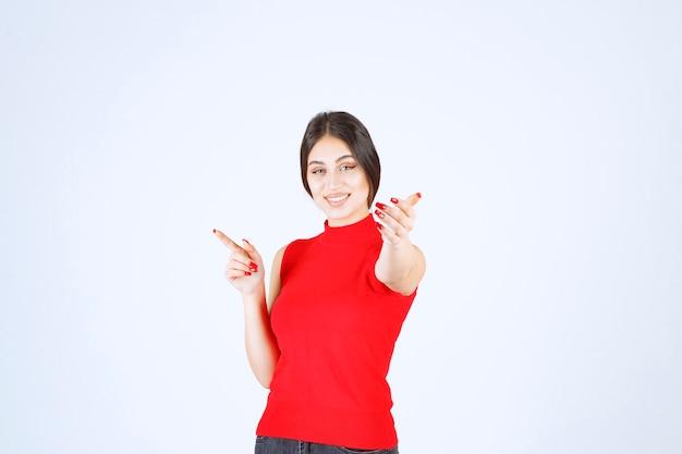 Menina de camisa vermelha, percebendo alguém à frente e cumprimentando-o.