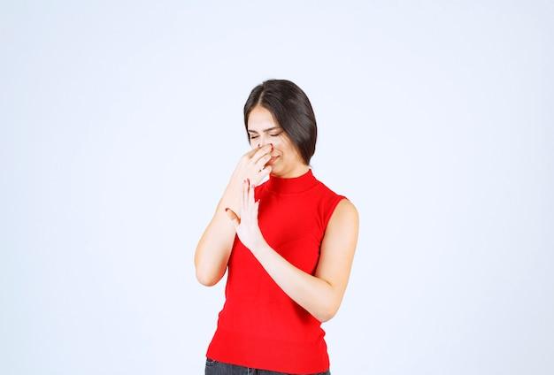 Menina de camisa vermelha prendendo a respiração por causa do mau cheiro.