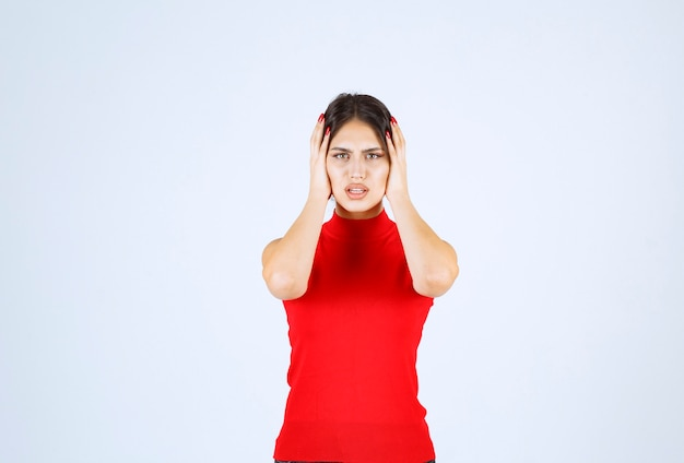 Menina de camisa vermelha, segurando a cabeça dela com as mãos, pois ela tem dor de cabeça.