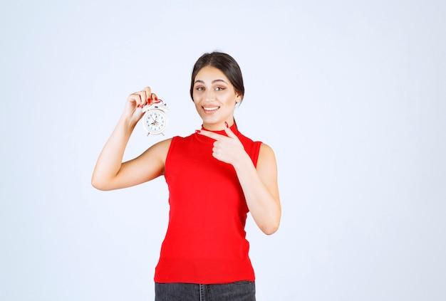 Menina de camisa vermelha segurando e promovendo um despertador.
