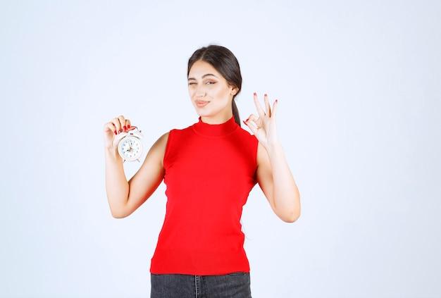Menina de camisa vermelha segurando um despertador e apreciando o produto.