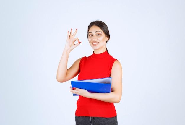 Menina de camisa vermelha, segurando uma pasta de negócios azul.