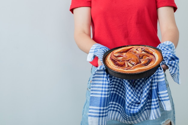 Menina de camisa vermelha segurando uma torta em uma assadeira preta