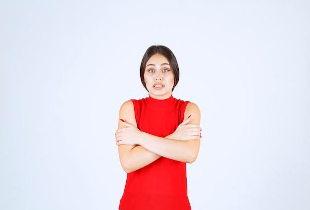 Menina de camisa vermelha, sentindo frio e enjoo.