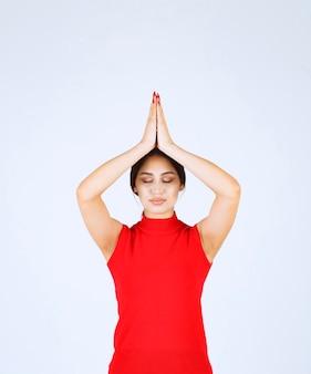 Menina de camisa vermelha, unindo as mãos e orando.